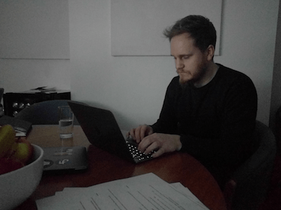 Person using a laptop sitting in a dim room