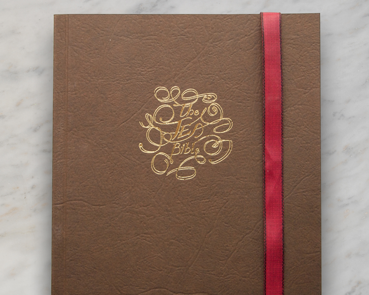 A leather effect book cover with a golden foil debosed script style motif
